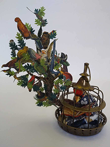 Anthropomorphic Sculpture of a Bird headed woman reading a book, sitting in her cage on a tree branch